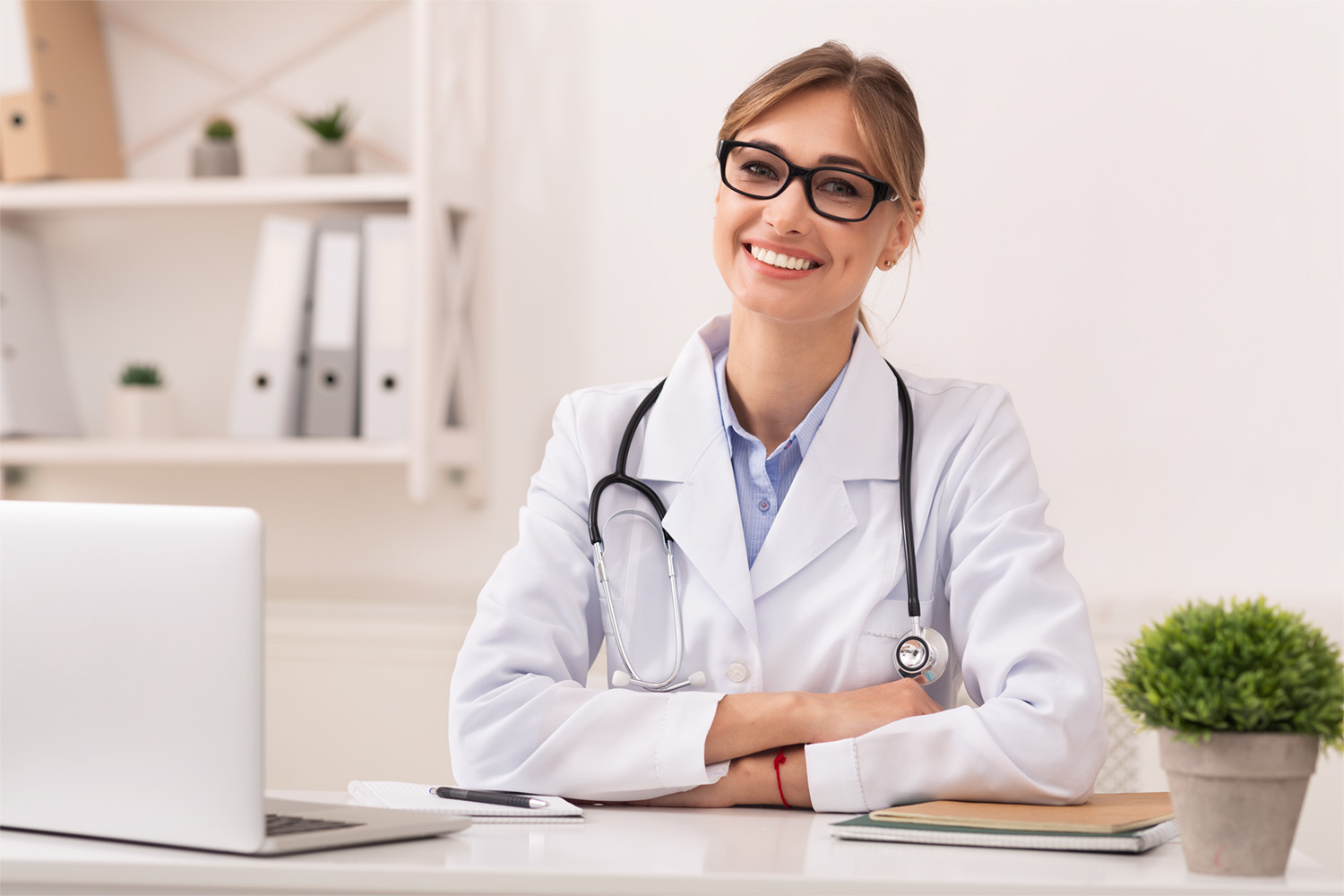 Family Doctor. Confident Lady Therapist Smiling At Camera Sitting In Modern Clinic Office.