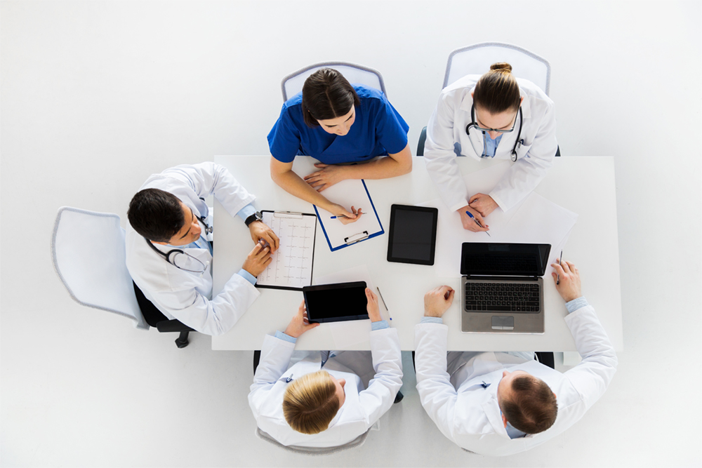 medicine, healthcare and cardiology concept - group of doctors with cardiogram, clipboard, tablet pc and laptop computers at hospital