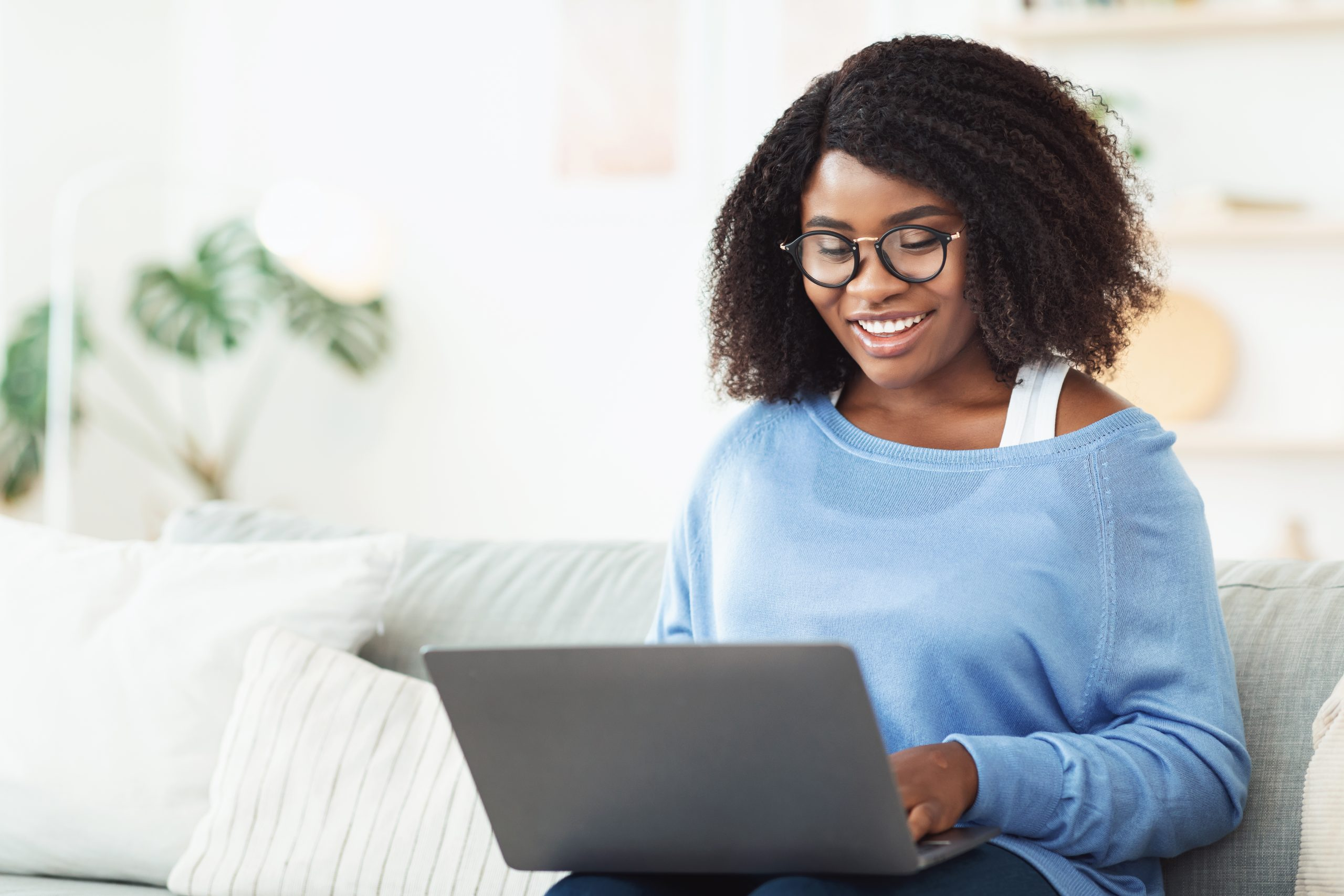 Enjoying The Day. Smiling black girl in eyewear typing on her laptop keyboard, sitting on couch, free space